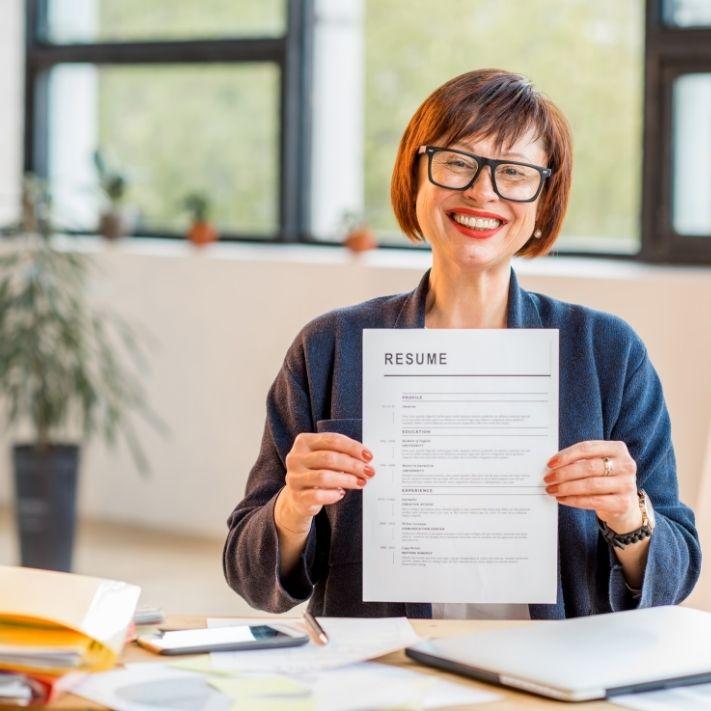 Frau hält glücklich ihre Bewerbungsunterlagen in den Händen