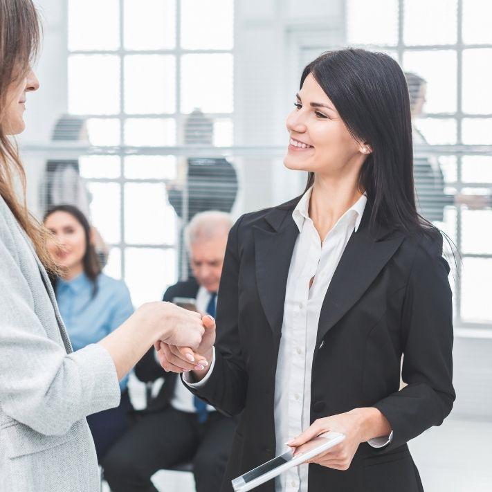 Frau wird befördert und besiegelt es mit der Chefin per Handschlag